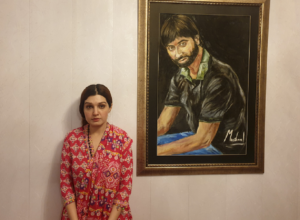 A portrait image of Mushaal Hussein Mullick with a painting of Mr. Yaseen Malik